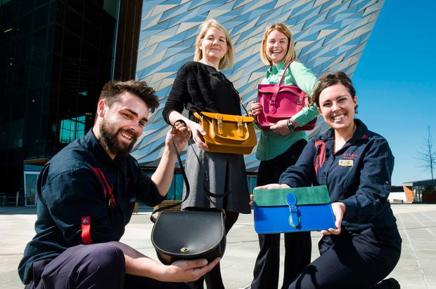 Standing are Laura Warrington, from USEL, and Denise Kennedy, from Titanic Belfast, who are helped to show off the satchels by Titanic Belfast staff Jack McGee and Nikita McGuinness