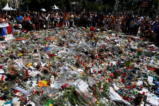 People gather at the memorial after a minute's silence on the Promenade des Anglais in Nice yesterday