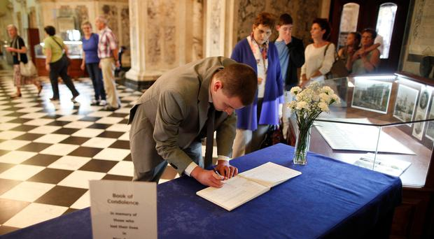 Members of the public sign the Belfast City Hall book of condolences for the victims of the atrocity in Nice last week