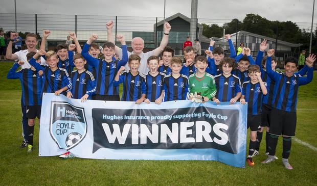 United mission: Deputy First Minister Martin McGuinness celebrates with his grandson Oisin Hargan and his Oxford United Stars team-mates after reaching the Under-13 semi-finals in the Hughes Insurance Foyle Cup at St Columb's Park, Derry