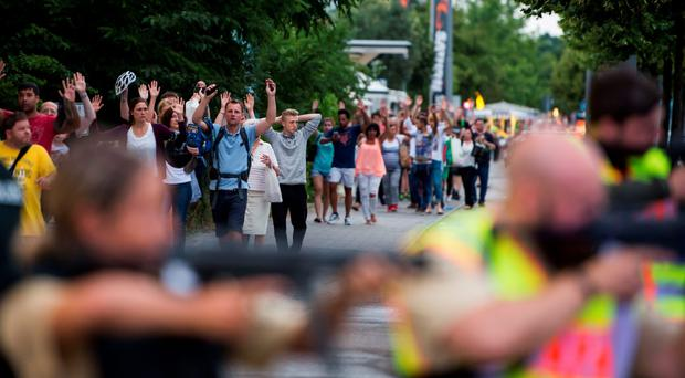 Police escort evacuated people from the shopping mall (the Olympia Einkaufzentrum (OEZ) in Munich on July 22, 2016 following a shootings earlier. AFP/Getty Images