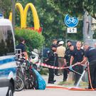 Police stand at a the crime scene where a shooting took place in front of a fast food restaurant leaving nine people dead the day before on Saturday, July 23, 2016 in Munich, Germany. (AP Photo/Sebastian Widmann)