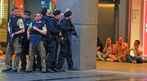 In this Friday, July 22, 2016 photo provided by Wael Ladki people take shelter as armed police officers are on the hunt for possible fugitives after a shooting in a shopping mall in Munich, southern Germany. A gunman killed 9 people before killing himself. (Wael Ladki via AP)