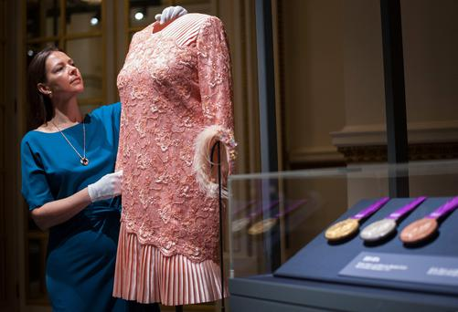 Curator Caroline de Guitaut adjusts a peach cocktail dress designed by Angela Kelly and worn by Queen Elizabeth II's at the opening Ceremony of the London 2012 Olympic games, during a press preview for Fashioning a Reign: 90 Years of Style from The Queen's Wardrobe, an exhibition at Buckingham Palace in London. PRESS ASSOCIATION Photo. Picture date: Thursday July 21, 2016. See PA story ROYAL Dresses. Photo credit should read: Lauren Hurley/PA Wire