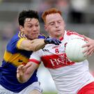 Eyes on the ball: Derry's Conor McAtamney with Ciaran McDonald of Tipperary while Derry's Thomas Mallon
