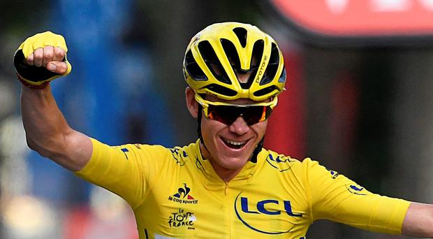 Just champion: Chris Froome lifts after the final stage in Paris