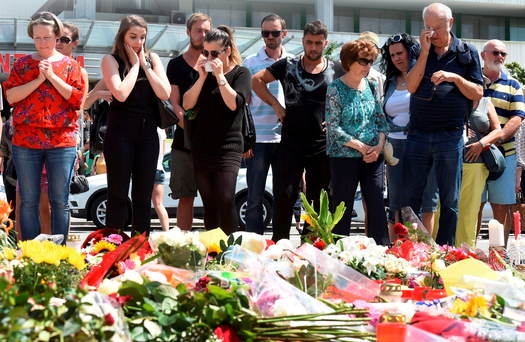 People mourn at a memorial of candles and flowers in front of the Olympia Einkaufszentrum shopping centre in Munich