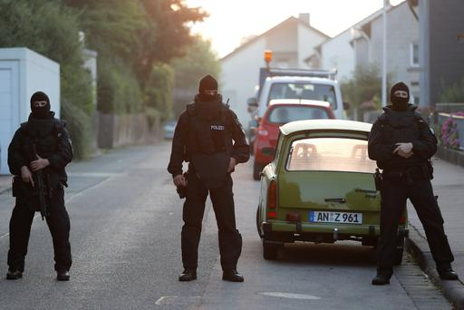 Special police officers secure a street near the house where a Syrian man lived before the explosion in Ansbach, southern Germany, Monday, July 25, 2016. The man who blew himself up and injured a dozen of people after being turned away from an open-air music festival was a 27-year-old Syrian who had been denied asylum, Bavaria's top security official said early Monday. (AP Photo/Matthias Schrader)