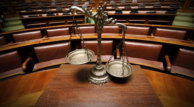 A woman was allegedly attacked and kicked out of a car travelling at speed in west Belfast, the High Court has heard