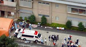 Ambulance crews and police at the scene of the mass stabbing. (Kyodo News via AP)