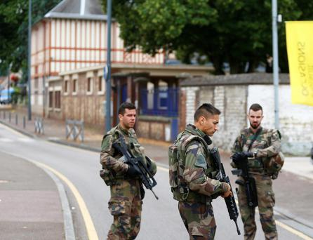 French soldiers stand guard as they prevent the access to the scene of an attack in Saint Etienne du Rouvray, Normandy, France, Tuesday, July 26, 2016. Two attackers invaded a church Tuesday during morning Mass near the Normandy city of Rouen, killing an 84-year-old priest by slitting his throat and taking hostages before being shot and killed by police, French officials said. (AP Photo/Francois Mori)