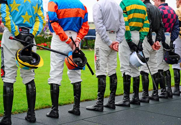 Jockeys and racegoers stand for a minute's silence in memory of John Thomas McNamara