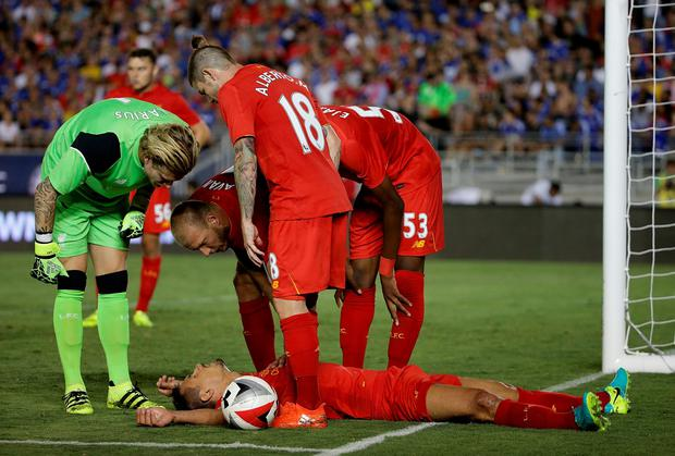 Dejan Lovren of Liverpool lays on the ground as his teammates tend to him in the second half against Chelsea during the 2016 International Champions Cup at Rose Bowl on July 27, 2016 in Pasadena, California. Chelsea defeated Liverpool 1-0. (Photo by Jeff Gross/Getty Images)
