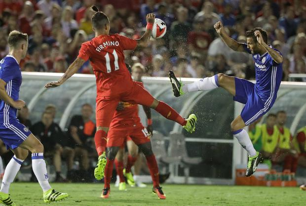 Liverpool's Roberto Firmino (11) and Chelsea's Cesc Fabregas, right, leap for the ball during the first half of an International Champions Cup soccer match at the Rose Bowl, Wednesday, July 27, 2016, in Pasadena, Calif. (AP Photo/Jae C. Hong)