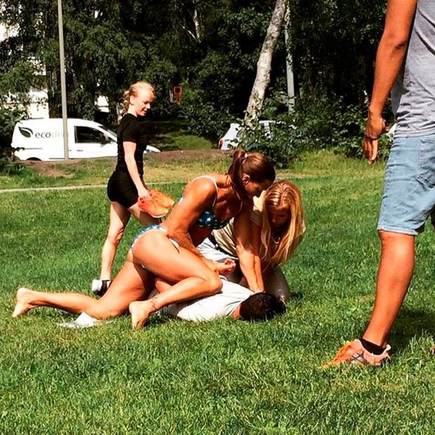 In this photo provided by Jenny Kitsune Adolffson Swedish police officer Mikaela Kellner is pinning a man to the ground who is suspected to have stolen a friend's mobile phone as she said, in Stockholm Sweden, Wednesday, July 27, 2016. (Jenny Kitsune Adolfsson via AP)