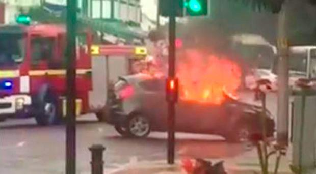 Handout still taken from video issued by Mel McDonough of a burnt out car outside Lloyds Bank in the High Street in Cheadle, Greater Manchester after armed robbers wielding a sledgehammer and chainsaw stormed the bank. PA