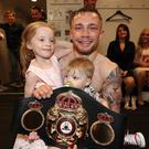 Carl Frampton pictured with his children Carla and Rossa and wife Christine in the background after defeating Leo Santa Cruz