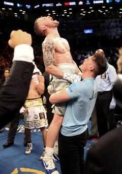 Carl Frampton being hoisted aloft after his sensational victory in the ring by trainer Shane McGuigan