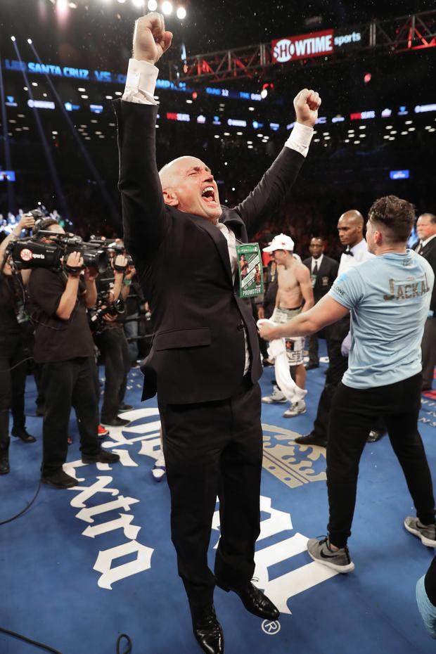 Carl's manager Barry McGuigan throws his arms in the air to celebrate the victory