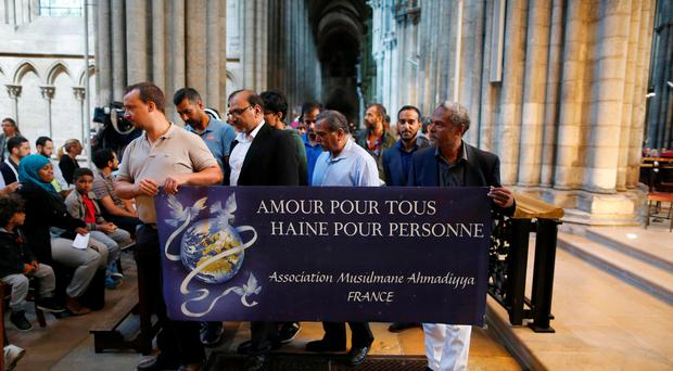Muslims hold a banner reading 'Love for all, hatred for no one' in tribute to slain priest