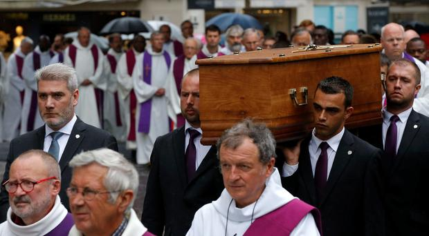 The coffin of Father Hamel is carried outside the Rouen cathedral, Normandy, before his funeral mass, Tuesday, Aug.2, 2016. Father Jacques Hamel, 85, was killed by two Islamic extremists last week in his church as he celebrated morning Mass. The Islamic State group claimed responsibility for the attack. (AP Photo/Michel Euler)