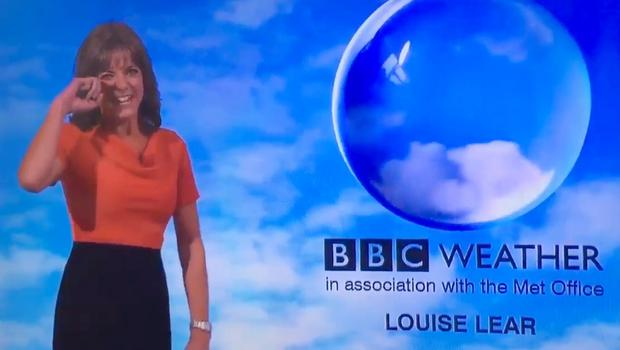 BBC News weather present Louise Lear wipes a tear away as she laughs during a forecast