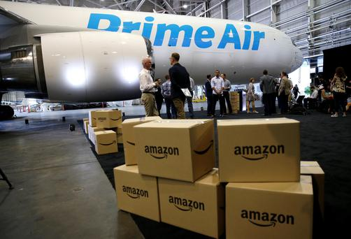 Amazon.com boxes are shown stacked near a Boeing 767 Amazon