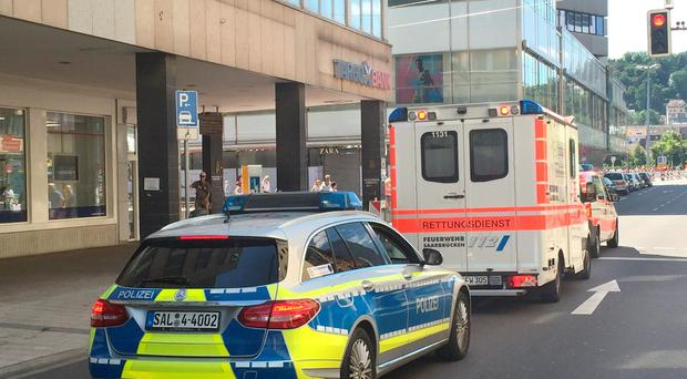 A policecar and an ambulance pictured in downtown Saarbruecken, Germany, Sunday Aug. 7, 2016. An injured man who barricaded himself in a restaurant in the western city of Saarbruecken on Sunday morning was later found asleep in the basement of the building and detained, police said. (Birgit Reichert/dpa via AP)