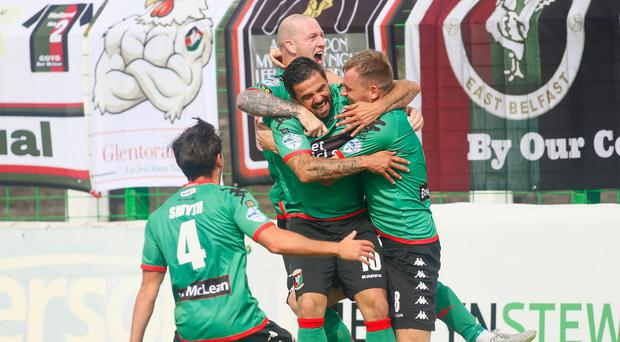 Net buster: Ciaran Caldwell is mobbed after blasting Glentoran's winner