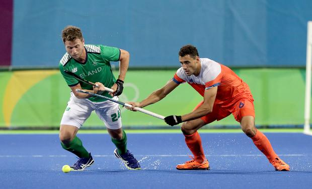 Stick 'em up: Ireland's Kyle Good clashes with Dutch defender Glenn Schuurman in last night's pool game in Rio