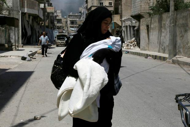 A woman carries her baby on a street as civilians fleeing the zones controlled by the Islamic State (IS) group arrive in the northern Syrian town of Manbij on August 7, 2016, a day after Syrian Democratic Forces (SDF) retook it from IS. AFP/Getty Images