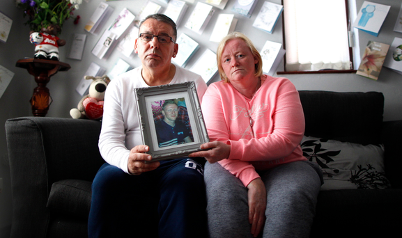 Heartbroken parents Elaine and Norman Little at their home with a portrait of their son Jonny (23), who died last week after taking his own life