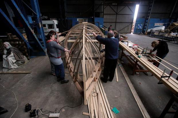 Volunteers take part in the construction of one of the largest currachs ever built, in the Titanic Quarter in Belfast, as it is nearing completion and will be finished next month. PA