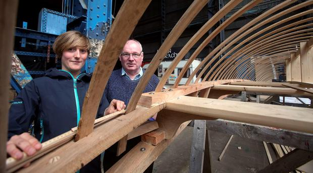 Volunteers Rachel Bolt (left) and Pat Hughes take part in the construction of one of the largest currachs ever built, in the Titanic Quarter in Belfast, as it is nearing completion and will be finished next month. PA