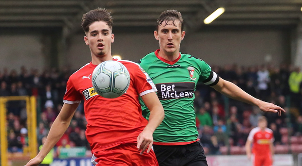 On the run: Cliftonville's Jay Donnelly is hunted down by Marcus Kane of Glentoran