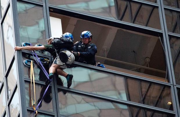 Police grab man scaling Trump Tower using suction cups on August 10, 2016 in New York. AFP/Getty Images