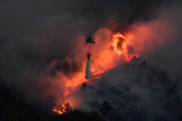 A helicopter carries an extinguisher in the struggle against a spreading fire near Vitrolles, southern France