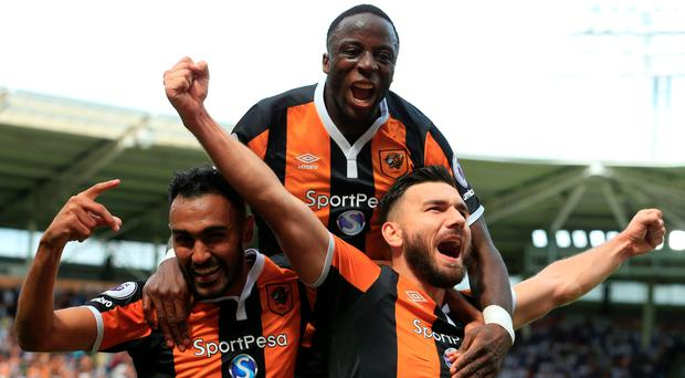 Hull City's Scottish midfielder Robert Snodgrass (R) celebrates with Hull City's Egyptian midfielder Ahmed Elmohamady (L) and Hull City's Norwegian striker Adama Diomande (C) LINDSEY PARNABY/AFP/Getty Images