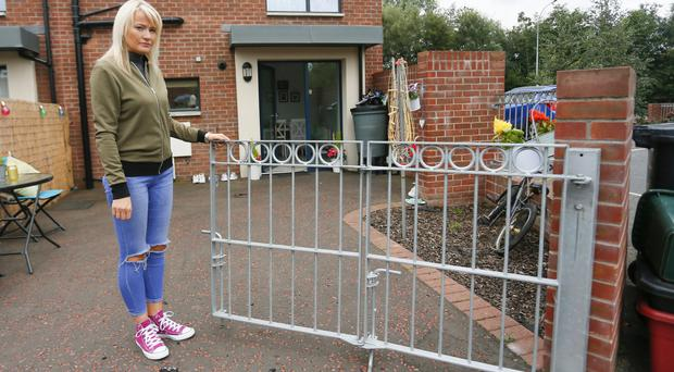 Pictured is the victim who wishes not to be named at her home in the Ormeau Embankment area of Belfast on the 13th August 2016 where her gates have been rammed and flammable liquid poured through her door ( Photo by Kevin Scott / Presseye )