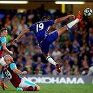 Chelsea's Diego Costa stretches for the ball in front of West Ham United's James Collins during the Premier League match at Stamford Bridge, London. PA