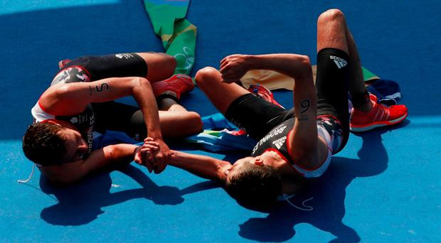 Alistair Brownlee and Jonathan Brownlee of Great Britain celebrate during the Men's Triathlon at Fort Copacabana on Day 13 of the 2016 Rio Olympic Games on August 18, 2016 in Rio de Janeiro, Brazil. (Photo by Adam Pretty/Getty Images)