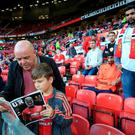 Manchester United fans read the matchday programme before the Premier League match at Old Trafford, Manchester. PA