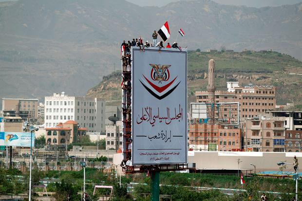 Yemeni wave the national flag atop a billboard during a gathering in support of the Huthi-led parliament, in the capital Sanaa on August 20, 2016. AFP/Getty Images