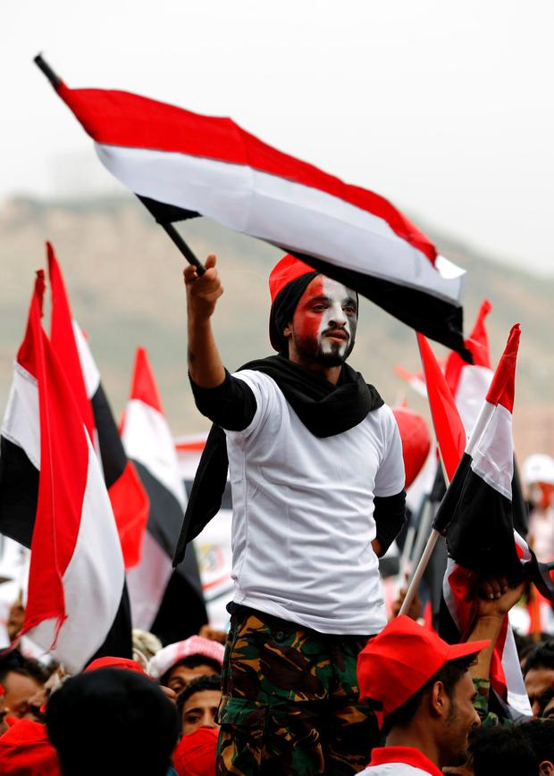 A Yemeni man waves the national flag during a gathering in support of the Huthi-led parliament, in the capital Sanaa on August 20, 2016. AFP/Getty Images
