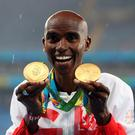 Double delight: Mo Farah shows off his 5,000m and 10,000m gold medals in Rio yesterday