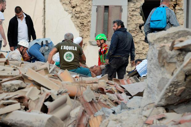 Rescuers help an injured victim among damaged buildings after a strong heartquake hit Amatrice on August 24, 2016. Central Italy was struck by a powerful, 6.2-magnitude earthquake in the early hours, which has killed at least three people and devastated dozens of mountain villages. Numerous buildings had collapsed in communities close to the epicenter of the quake near the town of Norcia in the region of Umbria, witnesses told Italian media, with an increase in the death toll highly likely. / AFP PHOTO / FILIPPO MONTEFORTEFILIPPO MONTEFORTE/AFP/Getty Images