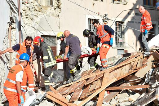 Rescuers clear debris while searching for victims in damaged buildings on August 24, 2016 in Arquata del Tronto, Italy. (Photo by Giuseppe Bellini/Getty Images)