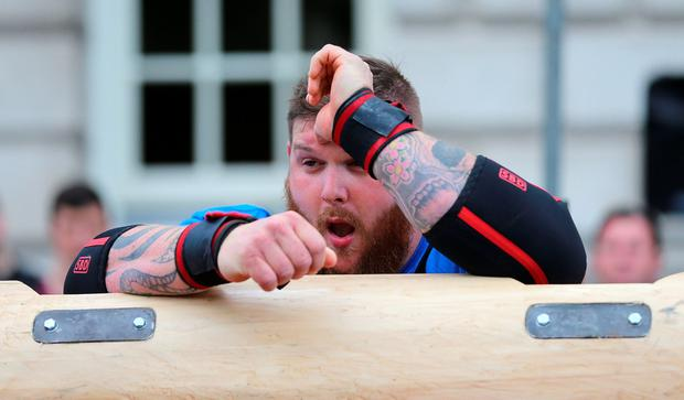 Aaron Page reacts after dropping a 150kg log on his head during the UK Strongest Man 2016 heats at Belfast City Hall, Belfast. PA
