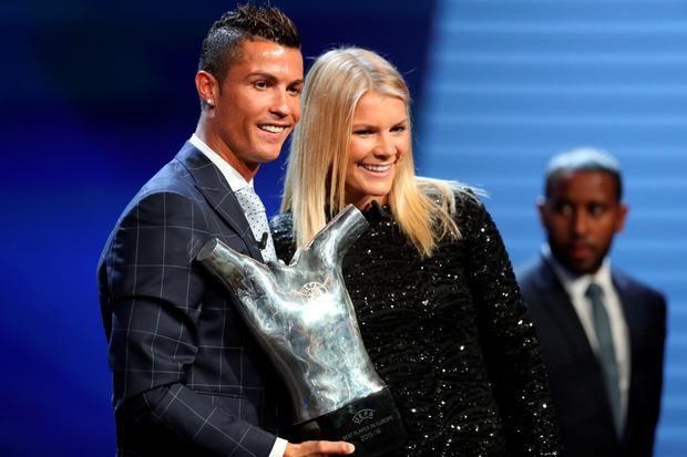 Real Madrid's Portuguese forward Cristiano Ronaldo (L) poses with Lyon's Norwegian forward Ada Hegerberg as he holds his trophy of Best Men's player in Europe at the end of the UEFA Champions League Group stage draw ceremony, on August 25, 2016 in Monaco. AFP PHOTO / VALERY HACHEVALERY HACHE/AFP/Getty Images
