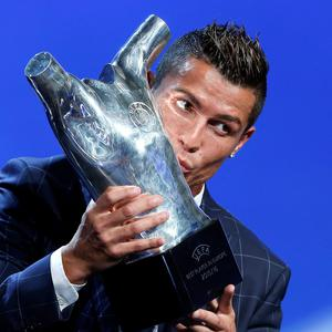 Real Madrid's forward Cristiano Ronaldo of Portugal, kisses his trophy after winning the best player of the year award, during the UEFA Champions League draw, at the Grimaldi Forum, in Monaco, Thursday, Aug. 25, 2016. (AP Photo/Claude Paris)